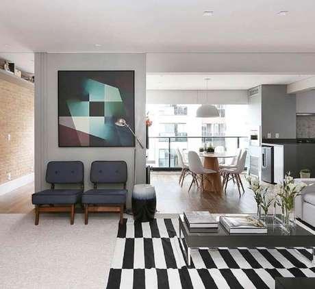32. Quadros decorativos grandes para sala com tapete listrado e decoração moderna
