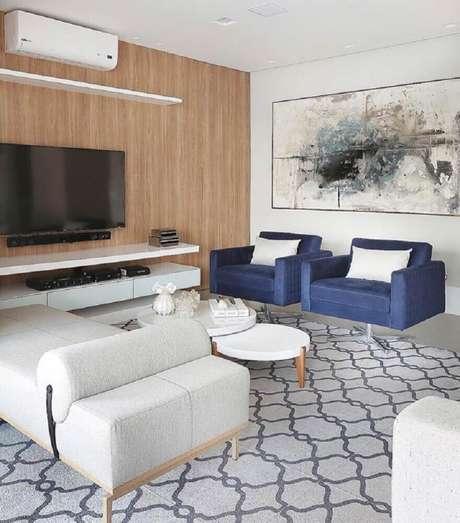 34. Quadros decorativos grandes para sala de estar com poltrona azul e parede revestida de madeira