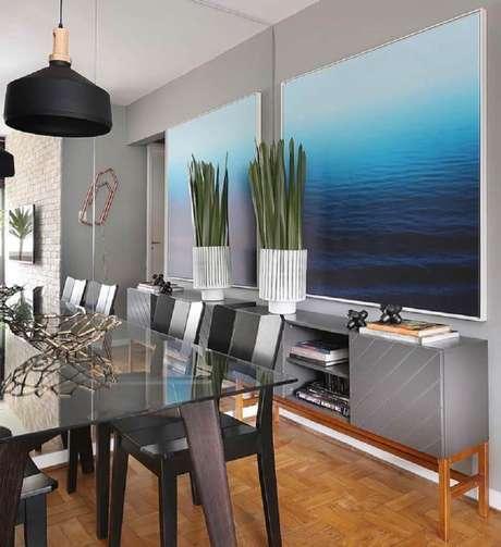 43. Mescle uma parede espelhada com quadros grandes para sala de jantar moderna