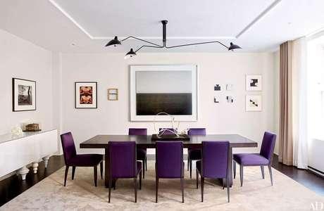 53. Sala de jantar com cadeiras roxas e quadros decorativos nas paredes