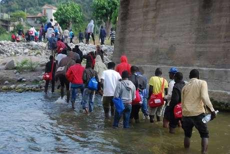 Deslocados externos marcham pelo rio Roja, em Ventimiglia, para chegar à fronteira com a França