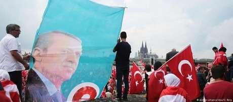 Adeptos de Erdogan portam sua efígie e bandeiras da Turquia, com a catedral de Colônia ao fundo