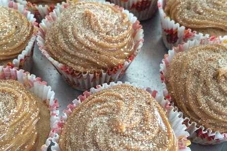 Cupcake de churros coberto com doce de leite e polvilhado com açúcar e canela