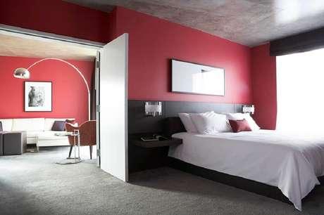 51. Esse quarto decorado resolveu utilizar uma cabeceira preta dando ainda mais destaque para a parede vermelha – Foto: Yandex