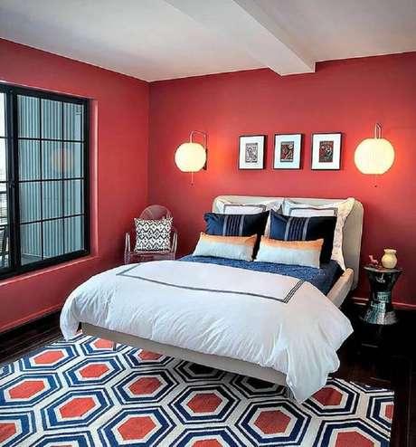 56. Decoração para quarto vermelho com tapete estampado e luminárias de parede ao lado da cama – Foto: Lauren M. Levine Interiors