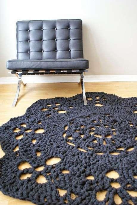 30. Um tapete de crochê preto combina perfeitamente com poltronas de couro