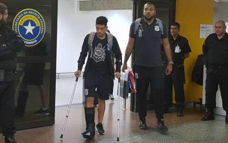 Na quinta-feira, Douglas voltou ao Brasil com muletas e bota para imobilizar o pé direito (Foto: Guilherme Amaro)