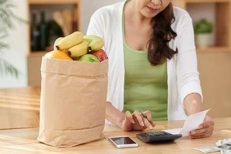 Moça calculando preço das compras de mercado