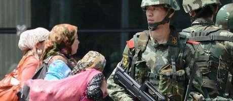 Policiais chineses patrulham bazar na província autônoma uigur de Xinjiang