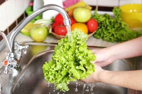 Folhas de alface sendo lavadas em água corrente