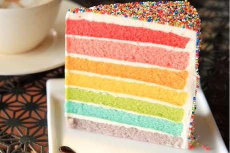 Fatia de bolo arco-íris em camadas com recheio e cobertura