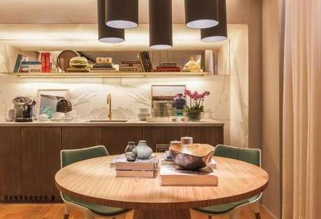 14. Cozinha planejada com mesa redonda de madeira e cadeiras verdes. Projeto de Bruno Gap