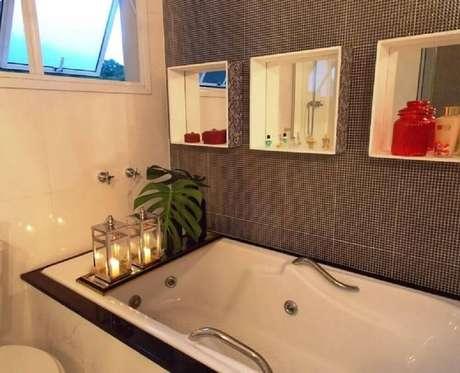 20. Decoração de banheiro com nicho com revestimento espelhado