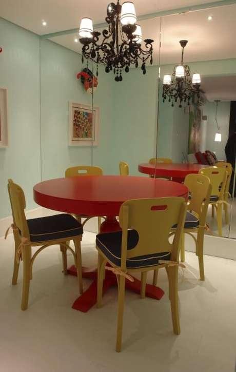 16. Mesa de jantar redonda e vermelha com cadeiras amarelas. Projeto de Luiz Humberto de Albuquerque