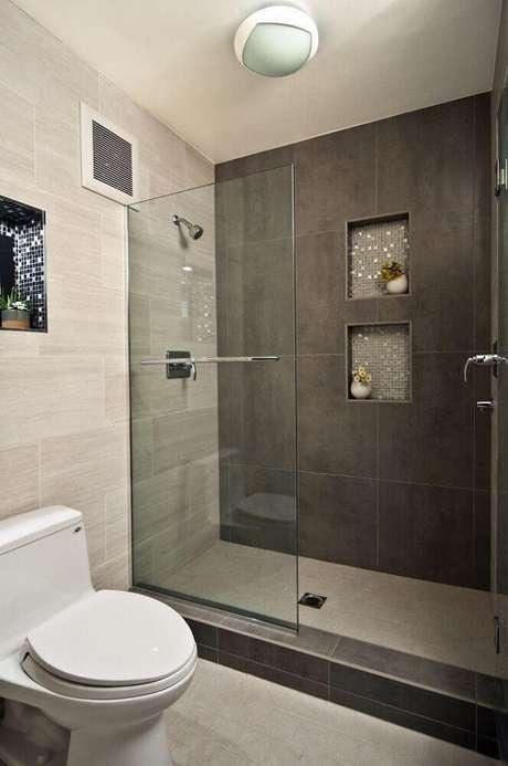 10. Linda decoração de nicho para banheiro em porcelanato com revestimento de pastilhas de vidro e pequenos vasinhos de flores.