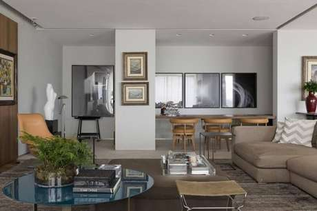 25. Sala de estar com mesa redonda baixa e puff grande no centro. Projeto de Roberto Migotto