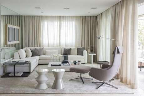 28. Sala de estar com mesa de canto grande preta e redonda. Projeto de Triplex Arquitetura