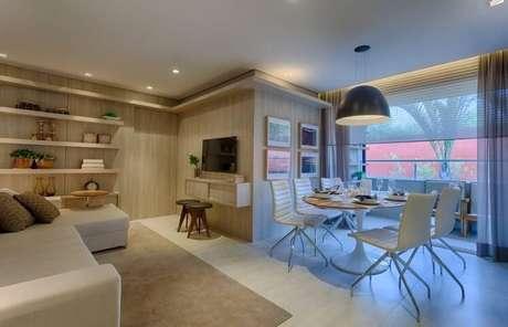 23. Sala de estar com mesa redonda de madeira e cadeiras brancas. Projeto de Renata Basques