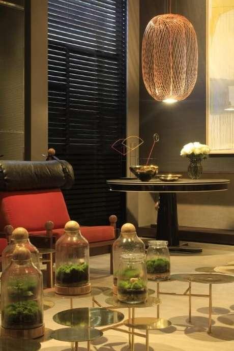 36. Sala de estar com mesa preta redonda e pendente acima. Projeto de Olegário de Sá