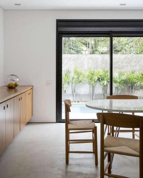 56. Sala de jantar com mesa redonda branca e cadeiras de madeira. Projeto de Felipe Hess