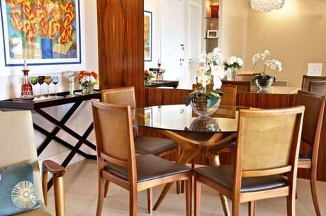46. Sala de jantar com mesa redonda de vidro e pés em madeira