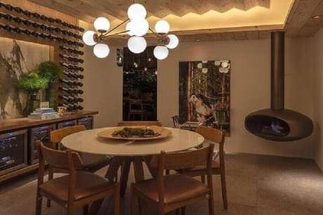 48. Mesa redonda de cor neutra e cadeiras de couro em sala sofisticada. Projeto de Bruno Gap