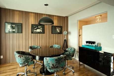 45. Sala de jantar com mesa redonda preta e poltronas coloridas. Projeto de Juliana Pippi