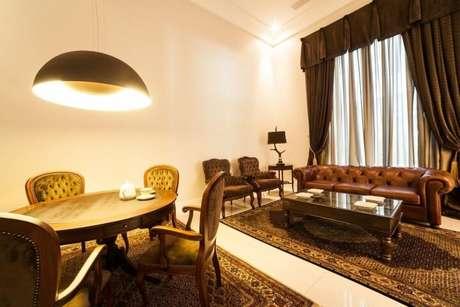 37. Sala integrada com decoração clássica e mesa de jantar redonda de madeira. Projeto de Bender Arquitetura