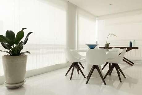 52. Varanda clean com mesa redonda e cadeiras brancas. Projeto de Marília Veiga