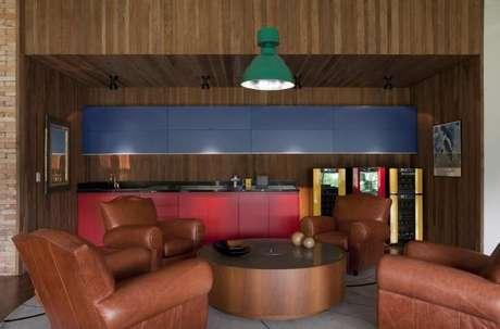 53. Varanda gourmet com mesa de centro redonda de madeira e poltronas de couro. Projeto de AMC Arquitetura