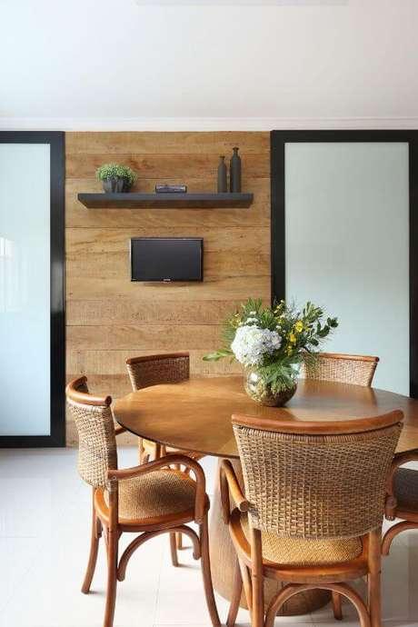 54. Varanda gourmet com mesa redonda de madeira e cadeiras de vime. Projeto de Bianchi Lima
