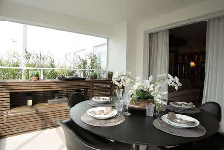 55. Mesa preta e cadeiras da mesma cor. Projeto de Carlos Rossi