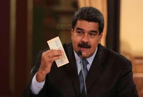 Presidente da Venezuela, Nicolás Maduro, segura nota da nova moeda do país, o bolívar soberano, durante reunião com ministros em Caracas 17/08/2018 Palácio de Miraflores/Divulgação via REUTERS