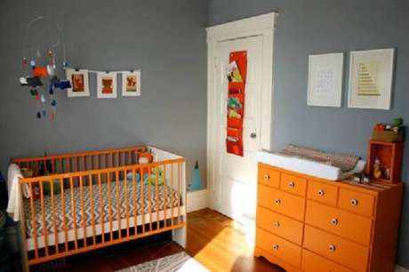 2. Decoração para quarto de bebê simples com paredes cinza e móveis pintados de laranja – Foto: Mami e Mais