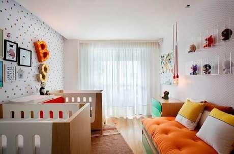 31. Decoração colorida e moderna para quarto de bebê gêmeos com papel de parede de bolinhas e nichos de acrílico – Foto: Cesar Valenccia