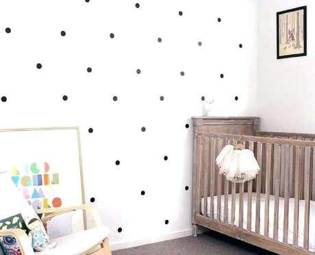 44. Decoração de quarto de bebê simples e barato com berço de madeira e papel de parede com estampa de bolinhas pretas – Foto: Pinterest