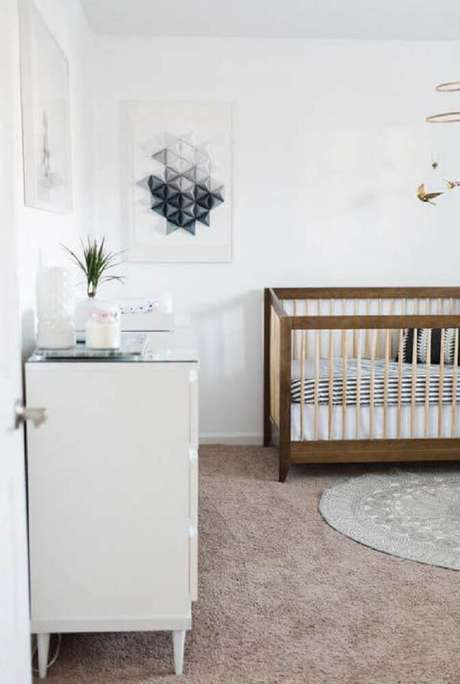 47. Aqui o minimalismo está presente tanto nos quadros quanto no berço de madeira e no tapete redondo para quarto de bebê simples e moderno – Foto: Home Decoo