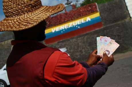 Cambista venezuelano exibe notas do 'Bolívar Soberano' em Roraima