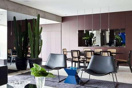 13. O vaso com cactos alto pode ser usado para dividir sala de jantar e sala de estar. Projeto por Suite Arquitetos.