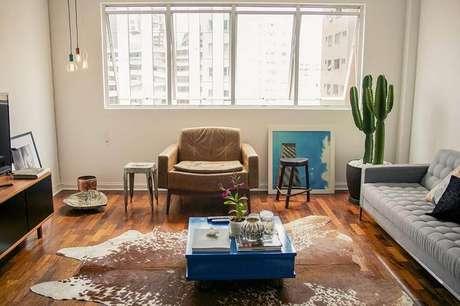 23. A sala de estar moderna tem um vaso de cactos altos perto da janela, assim a planta pode tomar sol. Projeto por Casa Aberta.