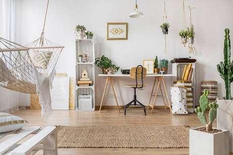 2. O home office escandinavo tem cactos altos em vasos de chão