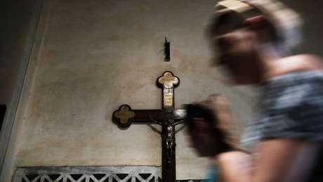 Mulher reza na Basílica de Santa Maria, em Roma; disputa entre alas da Igreja Católica extrapolou corredores do Vaticano para ser travada em público