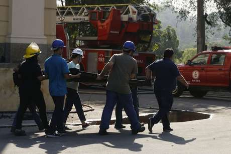 Pesquisadores e funcionários retiram peças dos escombros do Museu Nacional após incêndio