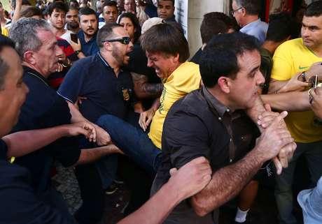 O candidato à Presidência da República pelo PSL, Jair Bolsonaro (de camiseta amarela), é socorrido após ser esfaqueado durante ato de campanha em Juiz de Fora (MG), nesta quinta-feira, 06. O presidenciável foi levado para o hospital.