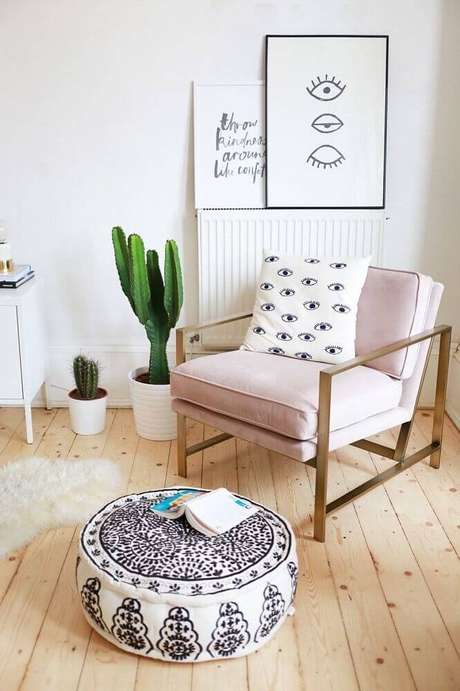 25. Decoração para cantinho de leitura com poltrona rosa e vaso de cactos – Foto: Brit + Co