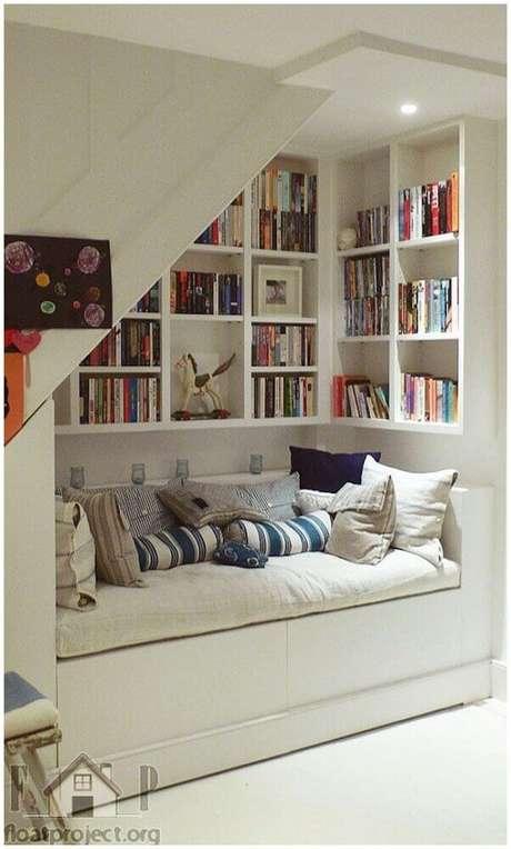 26. O espaço embaixo da escada pode se tornar um charmoso cantinho da leitura – Foto: Tile Design Gallery