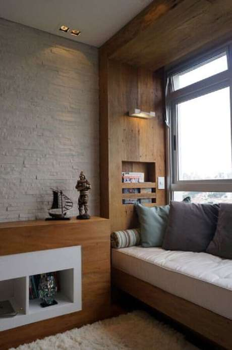31. Cantinho de leitura planejado com marcenaria ao lado da janela – Foto: Pinterest