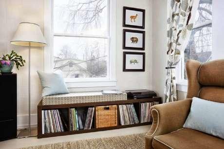 33. Cantinho da leitura na sala com nichos de madeira para livros e luminária de chão – Foto: Casay Diseno