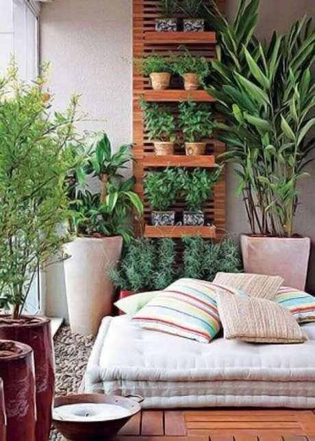 42. Cantinho da leitura na varanda decorado com jardim vertical, almofadas e futon – Foto: Farm Food Family