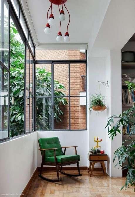 43. Decoração simples para cantinho da leitura na varanda com poltrona de balanço verde e vasos de planta – Foto: Pinterest
